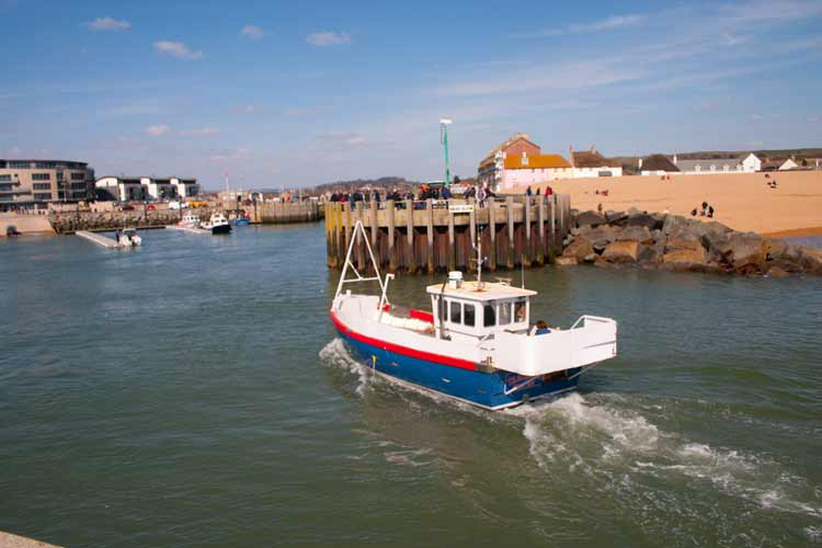 Fishing boat entering harbour at West Bay